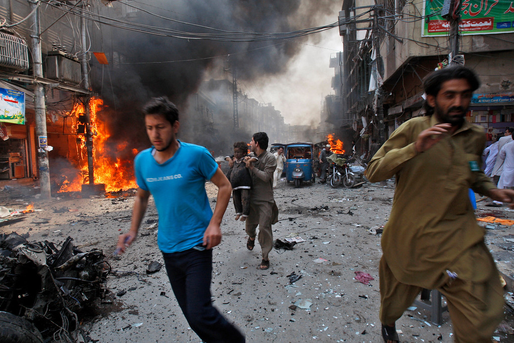 . Pakistani run away from the site of a blast shortly after a car explosion in Peshawar, Pakistan, Sunday, Sept. 29, 2013.  (AP Photo/Mohammad Sajjad)