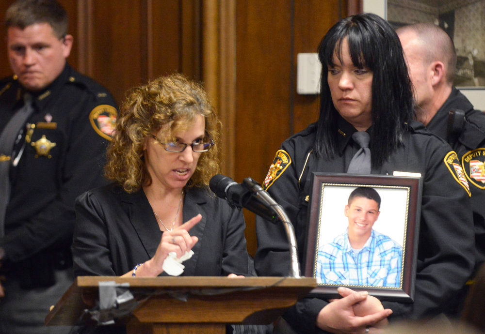 Description of . Dina Parmertor, mother of victim Daniel, speaks during the sentencing of T.J. Lane Tuesday, March 19, 2013, in Chardon, Ohio. Lane, was given three lifetime prison sentences without the possibility of parole Tuesday for opening fire last year in a high school cafeteria in a rampage that left three students dead and three others wounded. Lane, 18, had pleaded guilty last month to shooting at students in February 2012 at Chardon High School, east of Cleveland.  (AP Photo/The News-Herald, Duncan Scott, Pool)