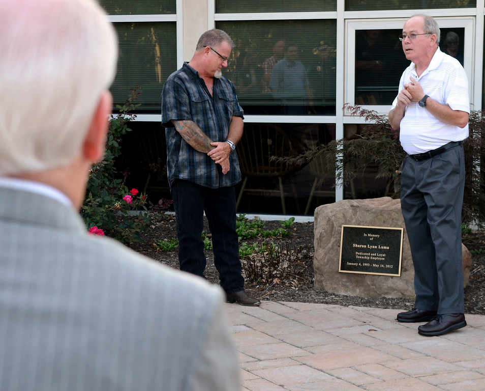 . Towamencin Township Board of Supervisors Chairman Daniel M. Littley, Jr.,R, speaks as memorial stone and plaque are dedicated to Sharon Luma, a former assistant to the Towamencin Township manager,who was killed in a motorcycle accident. Tim Luma ,L, her husband  along with friends and Towamencin Township officiials gathered for the ceremony at the township building on Wednesday August 27,2014. Photo by Mark C Psoras/The Reporter