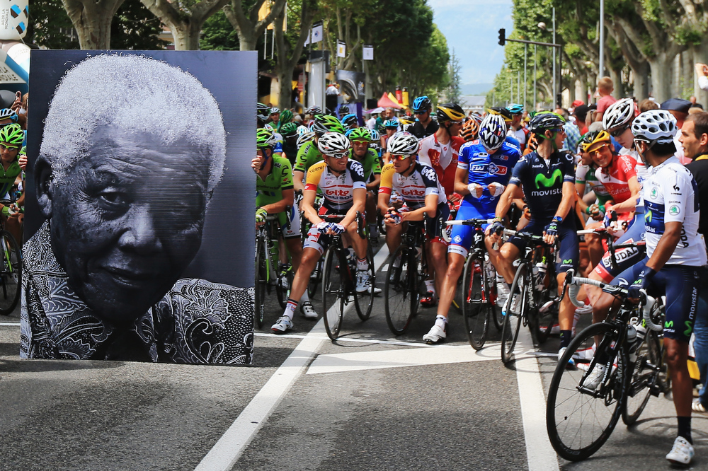 . The peloton waits behind a large picture commemorating the birthday of former South African President Nelson Mandela before stage eighteen of the 2013 Tour de France, a 172.5KM road stage from Gap to l\'Alpe d\'Huez, on July 18, 2013 in Gap, France.  (Photo by Doug Pensinger/Getty Images)