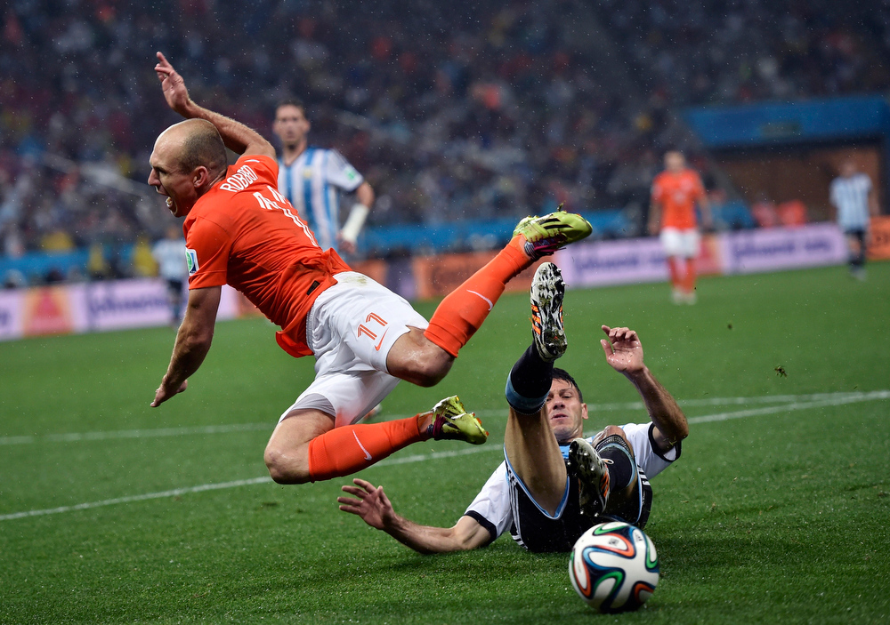 . Netherlands\' Arjen Robben goes down under a challenge from Argentina\'s Martin Demichelis during the World Cup semifinal soccer match between the Netherlands and Argentina at the Itaquerao Stadium in Sao Paulo Brazil, Wednesday, July 9, 2014. (AP Photo/Martin Meissner)