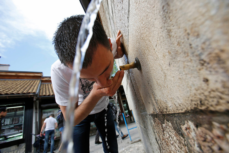 """. In this Tuesday, April 22, 2014, a Bosnian man drinks from a water pipe in the old town, known as Bascarsija, in Sarajevo, Bosnia-Herzegovina. Despite the dark chapters of the past, today the city is defined by what locals call the \""""Sarajevo Spirit\"""", an interesting and mostly harmonious mix of religions and cultures. (AP Photo/Amel Emric)"""
