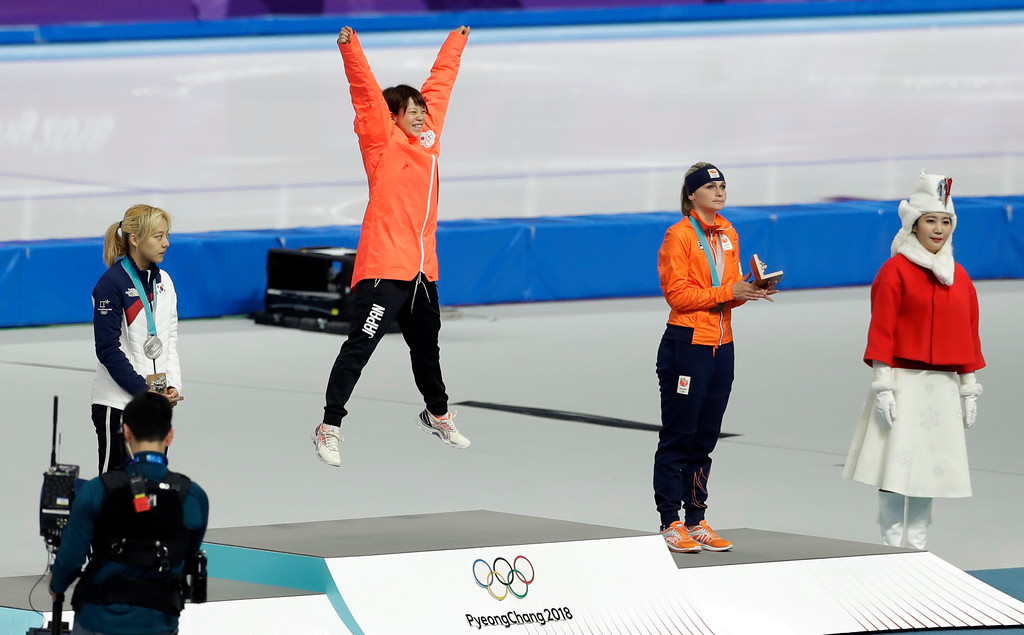 . Gold medalist Nana Takagi of Japan, center, silver medalist Kim Bo-reum of South Korea, left, and bronze medalist Irene Schouten of The Netherlands, second right, celebrate on the podium of the women\'s mass start speedskating race at the Gangneung Oval at the 2018 Winter Olympics in Gangneung, South Korea, Saturday, Feb. 24, 2018. (AP Photo/Petr David Josek)