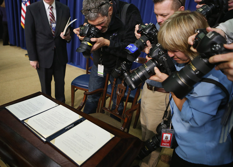 . WASHINGTON, DC - JANUARY 16:  News photographers make images of the executive orders U.S. President Barack Obama signed regarding the administration\'s new gun law proposals in the Eisenhower Executive Office building January 16, 2013 in Washington, DC. One month after a massacre that left 20 school children and 6 adults dead in Newtown, Connecticut, the president unveiled a package of gun control proposals that include universal background checks and bans on assault weapons and high-capacity magazines.  (Photo by Chip Somodevilla/Getty Images)