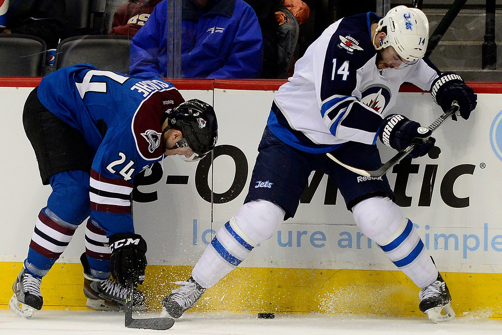 . Anthony Peluso (14) of the Winnipeg Jets loses control of the puck as Marc-Andre Cliche (24) of the Colorado Avalanche defends during the first period of action.  (Photo by AAron Ontiveroz/The Denver Post)