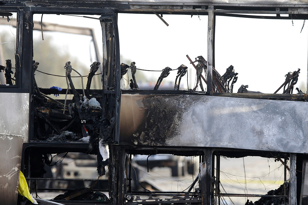 . The remains of a tour bus that was struck by a FedEx truck on Interstate 5 Thursday is shown in Orland, Calif., Friday, April 11, 2014. At least ten people were killed and dozens injured in the fiery crash between the truck and a bus carrying high school students on a visit to a Northern California College. (AP Photo/Jeff Chiu)