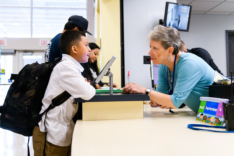 Office manager Eileen Monahan helps a student with his hall pass. Back to school day at Hallman Elementary School on Wednesday, September 4, 2019 in Salem, Ore.