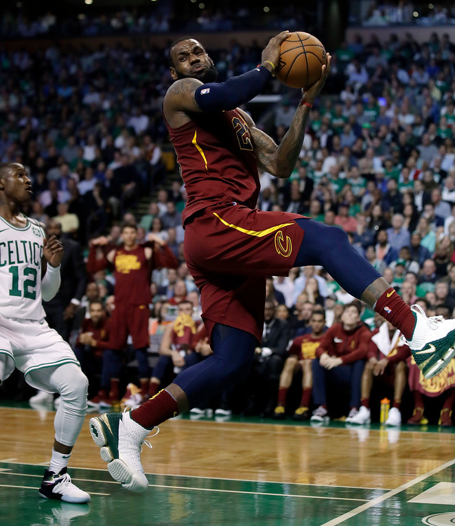 . Cleveland Cavaliers forward LeBron James recoils after colliding with Boston Celtics forward Jayson Tatum, out of picture, in front of Celtics guard Terry Rozier, left, during the first half in Game 2 of the NBA basketball Eastern Conference finals, Tuesday, May 15, 2018, in Boston. (AP Photo/Charles Krupa)