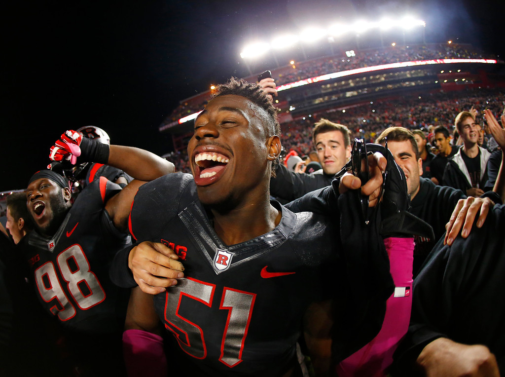 . Rutgers\' Daryl Stephenson (98) and Sebastian Joseph (51) celebrate as fans flood the field after Rutgers defeated Michigan 26-24 in an NCAA college football game Saturday, Oct. 4, 2014, in Piscataway, N.J. (AP Photo/Rich Schultz)