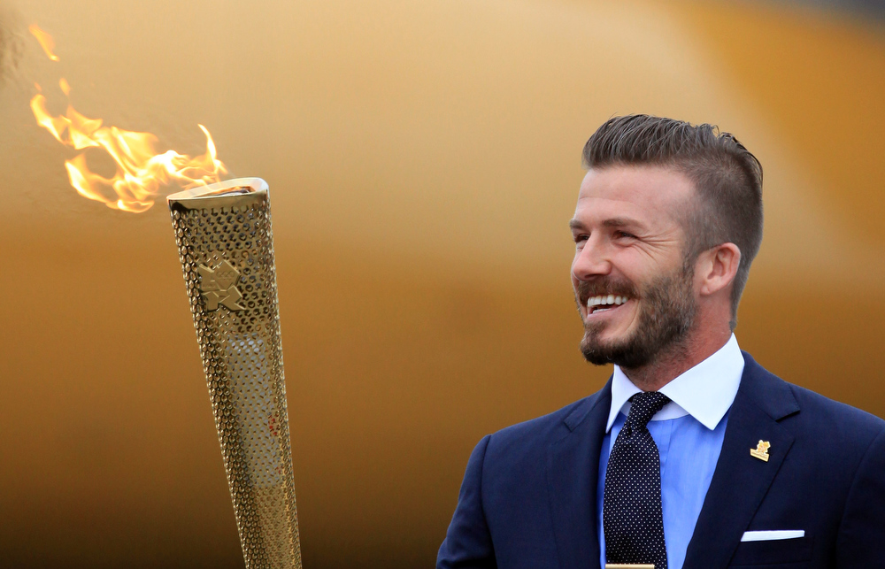 . David Beckham holds the Olympic Flame as it arrives at RNAS Culdrose near Helston on May 18, 2012 in Cornwall, England. The Olympic Flame arrived in the UK after it was handed over at a ceremony yesterday in Athens. A British delegation including David Beckham, flew back with the flame from Greece where they attended a ceremony welcoming the flame, before it is taken on a 70-day relay involving 8,000 torchbearers covering 8,000 miles.  (Photo by Matt Cardy/Getty Images)