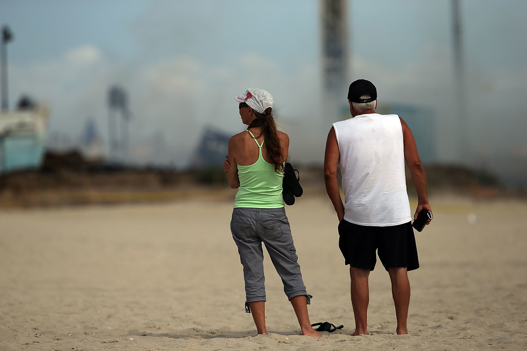 . Two people stand near the scene of a massive fire that destroyed dozens of businesses along an iconic Jersey shore boardwalk on September 13, 2013 in Seaside Heights, New Jersey. (Photo by Spencer Platt/Getty Images)