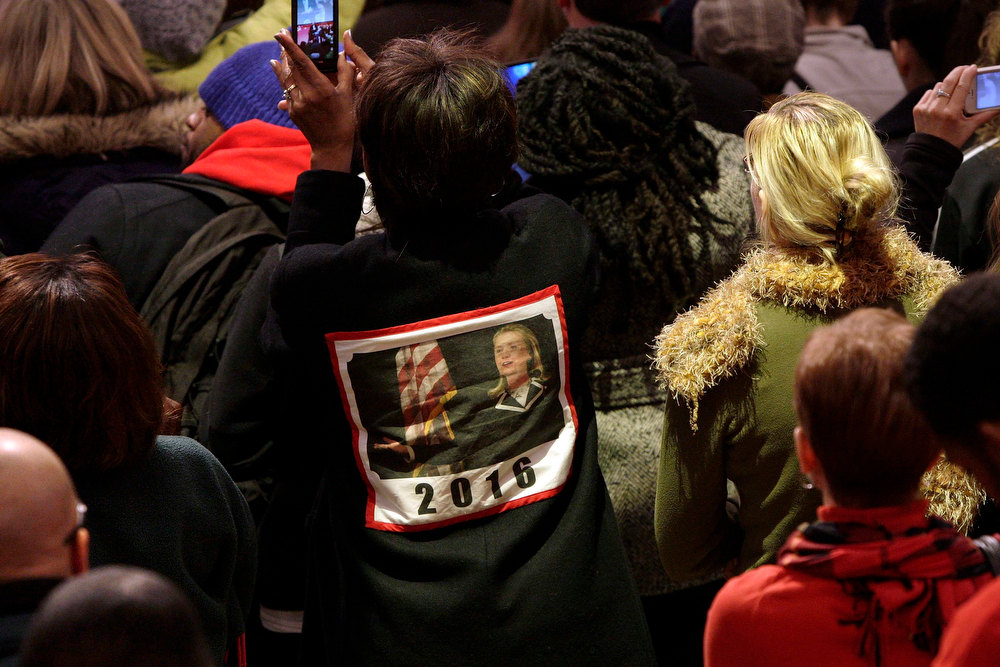 . A woman wears a coat with a picture of U.S. Secretary of State Hillary Clinton and the number 2016, a reference to the possibility she might run for president in 2016, as she listens to Vice President Joe Biden speak to volunteers at a Unite America in Service event at the National Guard Armory in Washington, January 19, 2013. Biden and his family volunteered to assemble care kits for U.S. service members and veterans at the event during the National Day of Service as part of the 57th Presidential Inauguration. REUTERS/Jonathan Ernst
