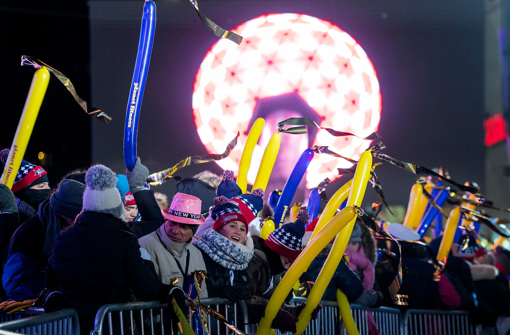 . With a television image of the ceremonial ball in the background, revelers gather on Times Square in New York, Sunday, Dec. 31, 2017, as they take part in a New Year\'s Eve celebration. (AP Photo/Craig Ruttle)