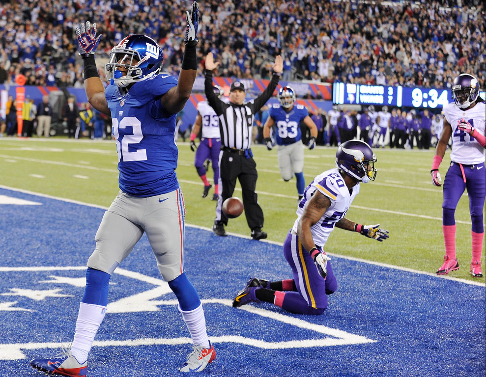 . New York Giants wide receiver Rueben Randle (82) celebrates after catching a pass for a touchdown as Minnesota Vikings cornerback Chris Cook (20) and Mistral Raymond (41) react during the first half of an NFL football game Monday, Oct. 21, 2013 in East Rutherford, N.J. (AP Photo/Bill Kostroun)