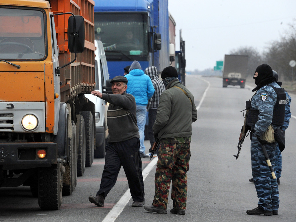 . Armed masked men who called themselves members of Ukraine\'s disbanded elite Berkut riot police force and and local militiamen patrol at a checkpoint on a highway that connect Black Sea Crimea  peninsula to mainland Ukraine near the city of Armyansk, on February 28, 2014. The sign on the bar reads: \'Fascism Shall Not Pass!\' The spiraling tensions in a nation torn between the West and Russia took today a severe new turn when Ukraine\'s interim president Oleksandr Turchynov accused Russian soldiers and local pro-Kremlin militia of staging raids on Crimea\'s main airport and another base on the southwest of the peninsula where pro-Moscow sentiments run high. AFP PHOTO / VIKTOR  DRACHEV/AFP/Getty Images