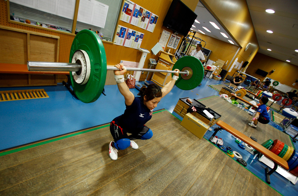 . In this Friday, Aug. 30, 2013 photo, Japanese weightlifter Hiromi Miyake, silver medalist in the London Olympic women\'s 48kg event, lifts weight during her training at one of Tokyo\'s leading training centers. The Olympics are in Miyake\'s blood, a heritage that stretches back to the 1960s, when her uncle won a gold medal at the 1964 Tokyo Games and her father won bronze in Mexico City in 1968. With the Olympics coming to Tokyo in 2020, she hopes that will inspire the next generation of Japanese athletes. (AP Photo/Junji Kurokawa)