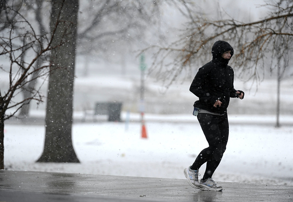 . A woman braves wet snowflakes as she jogs along Louisiana Ave and near Franklin St. at Washington Park Saturday  morning,  March 9th, 2013. Andy Cross, The Denver Post