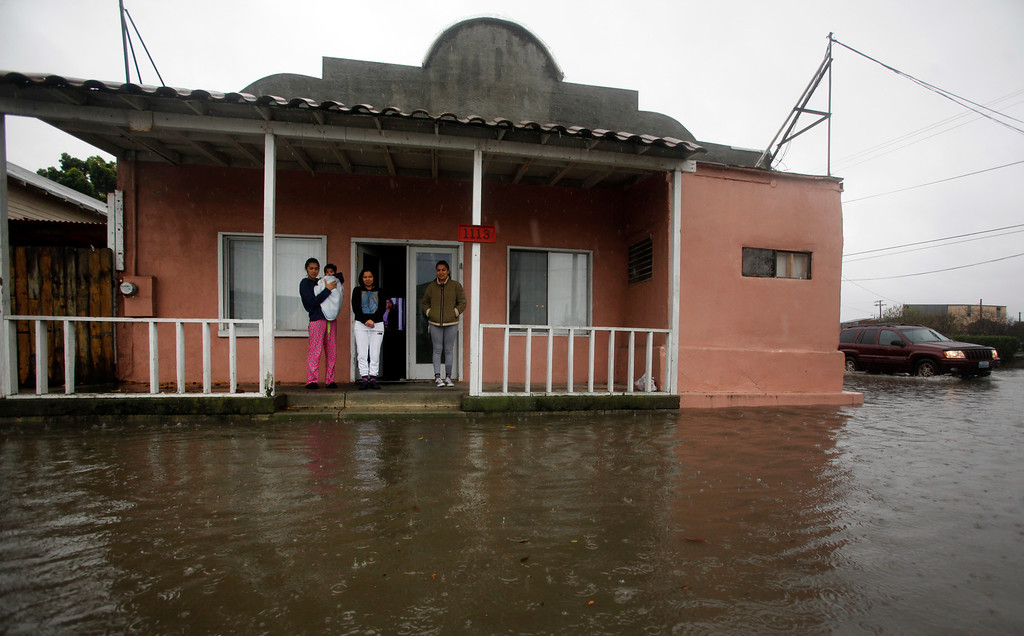 . The De La Torre family watches from their Taylor Street doorstep as waters rise around their home in Alviso, Calif., Thursday, Dec. 11, 2014. (Karl Mondon/Bay Area News Group)