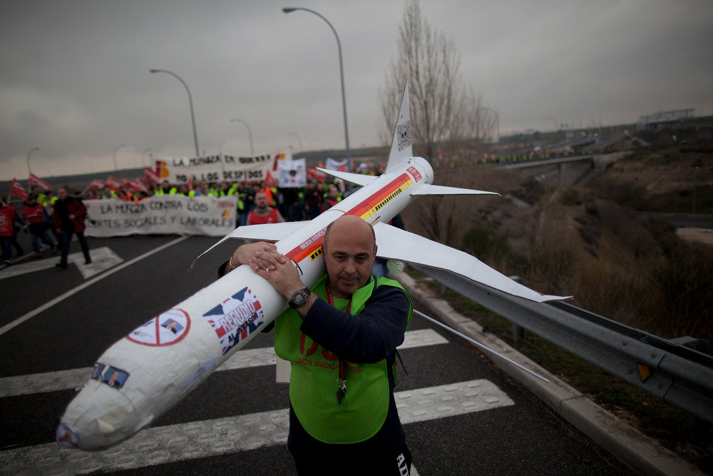 . A member of the Spanish Airline Iberia carries a model plane during a protest against job cuts at Barajas Airport on February 18, 2013 in Madrid, Spain. Today is the first of a five day strike held by Iberia cabin crew, maintenance workers and ground staff in response to the planned loss of 3,800 jobs. The strike has resulted in the airline having to cancel 400 flights this week with unions planning a further five day strikes within a month.  (Photo by Pablo Blazquez Dominguez/Getty Images)