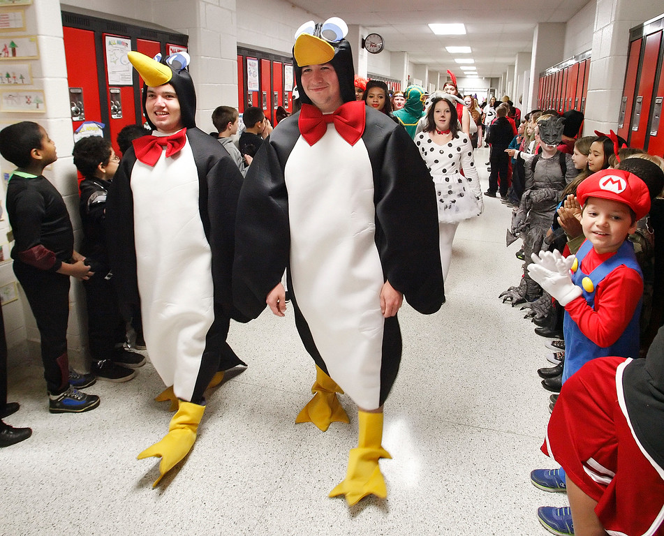 . Port Jervis High School seniors walk through the halls of Anna S. Kuhl Elementary School during the Halloween Parade, a tradition for more than 30 years, Thursday, Oct. 31, 2013 in Port Jervis, N.Y. The parade starts with the seniors walking through hallways lined with elementary school students and ends with the elementary school students walking through a line of seniors in front of the high school.  (AP Photo/Times Herald-Record, Tom Bushey)