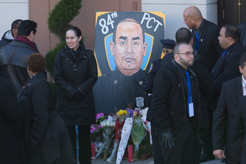 . A portrait of New York Police Department (NYPD) officer Rafael Ramos is placed outside his funeral at the Christ Tabernacle Church on December 27, 2014 in the Glenwood section of the Queens borough of New York City. Ramos was shot, along with Police Officer Wenjian Liu while sitting in their patrol car in an ambush attack in Brooklyn on December 20. Thousands of fellow officers, family, friends and Vice President Joseph Biden arrived at the church for the funeral.  (Photo by Kevin Hagen/Getty Images)