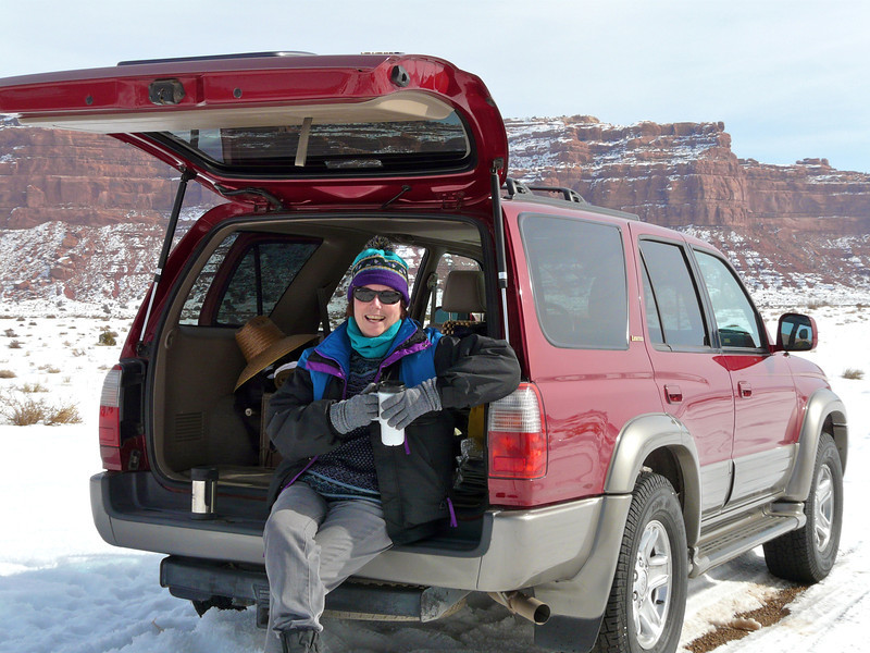 Woman sits in the trunk of an SUV on a snowy road.