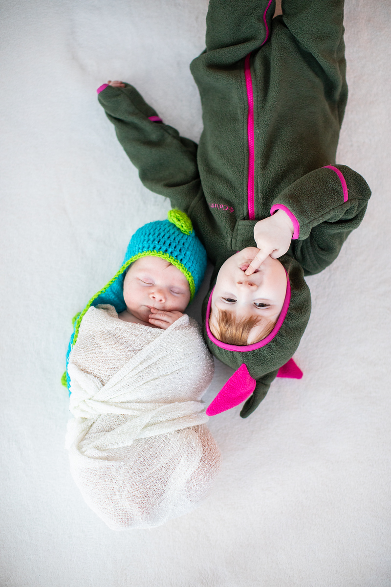 Washington DC newborn photographer Jalapeno Photography features baby Amelia's photos. This photo is of the beautiful baby in a knit monster hat with her sister in a monster outfit.