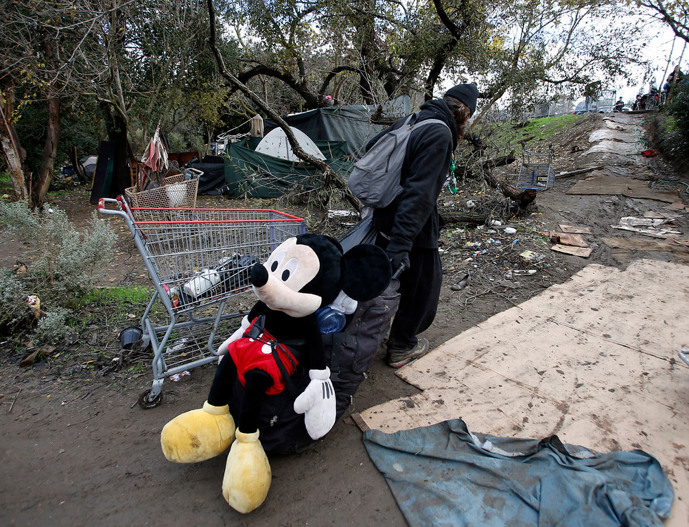 """. Dragging a large Mickey Mouse doll, Erich Von Shultz leaves his home in The Jungle homeless camp closed by city officials Thursday morning, Dec. 4, 2014, in San Jose, Calif. He dragged what possessions he could, saying, \""""You can\'t leave Mickey Mouse behind.\"""" (Karl Mondon/Bay Area News Group)"""