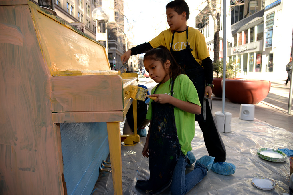 . Analytic Lopez, 9, front, and Jeremy Leal, 9, of Denver Center for International Studies at Fairmont are painting the piano on the 16th street mall. Denver, Colorado November 21, 2014. Elementary students from DCIS at Fairmont and Downtown Denver Expeditionary School are painting the town in holiday colors on the 16th Street Mall. A group of students, along with their teachers, painted five pianos as part of the Downtown Denver Business Improvement District�s Your Keys to the City Program. (Photo by Hyoung Chang/The Denver Post)