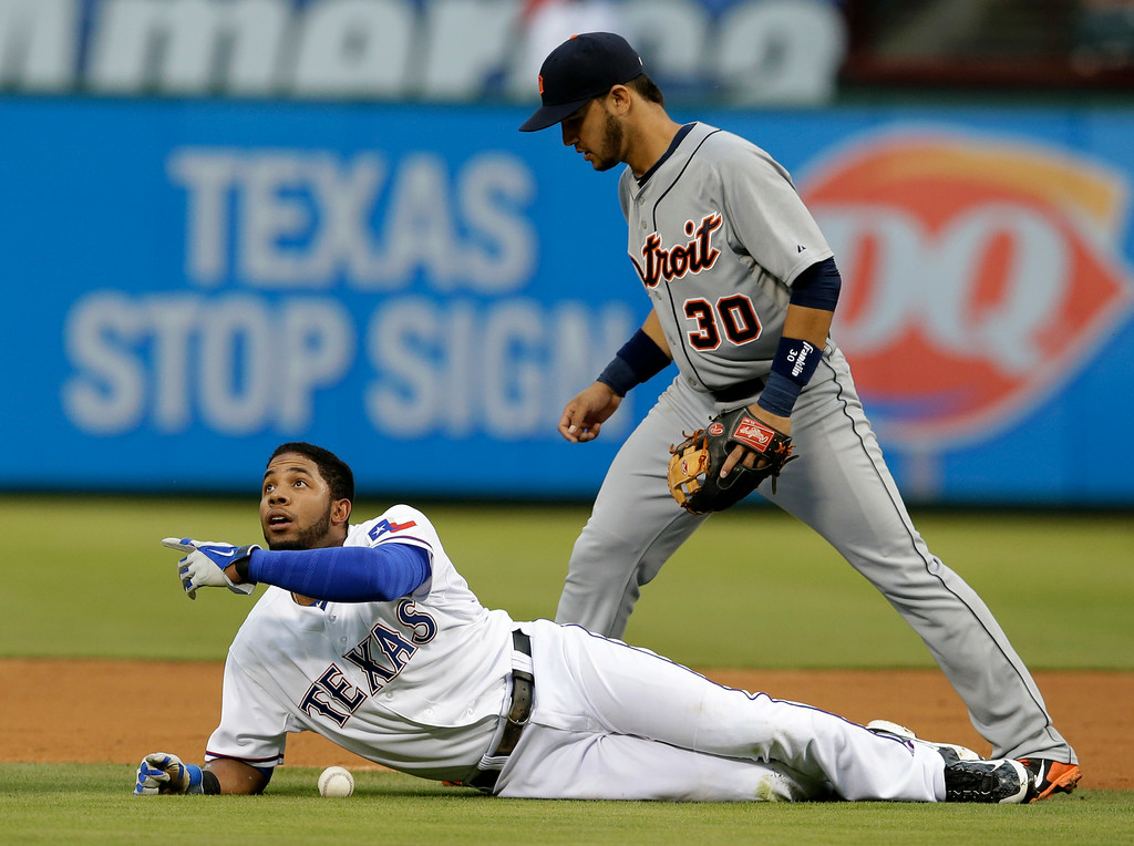 . Texas Rangers\' Elvis Andrus lays on the ground after being called out looking up at second base umpire Clint Fagan, not pictured, as Detroit Tigers shortstop Eugenio Suarez (30) searches for the ball in the first inning of a baseball game, Tuesday, June 24, 2014, in Arlington, Texas. Andrus was caught in a run down attempting to steal second on the play. (AP Photo/Tony Gutierrez)