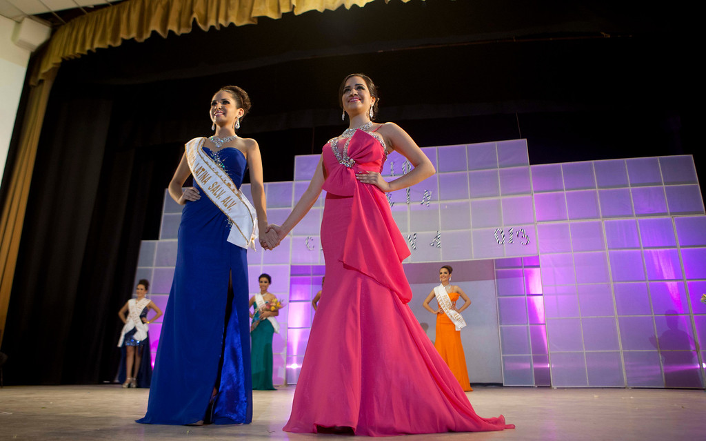 ". In this Jan. 26, 2013 photo, Donaji Lopez, 17, left, and Magdabelyn Porra Gamez, 18, hold hands awaiting the decision of the winner the ""Guamuchil Carnival Queen 2013\"" beauty contest in Guamuchil, Sinaloa state. Porra\'s cousin Susana Flores Gamez who was voted the 2012 Woman of Sinaloa in a beauty pageant in February, was killed in northern Mexico on Nov. 24, 2012 during a gun battle between soldiers and the gang of drug traffickers she was traveling with. (AP Photo/Eduardo Verdugo)"