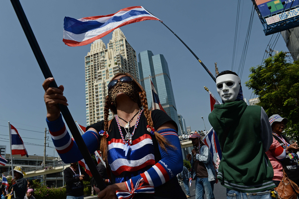 . Thai anti-government protesters wave national flags as they march as part of their ongoing rallies in downtown Bangkok on January 21, 2014.  Demonstrators have been staging \'shutdown\' protests for more than a week in the Thai capital in their bid to force Prime Minister Yingluck Shinawatra from power and topple her government.  (CHRISTOPHE ARCHAMBAULT/AFP/Getty Images)