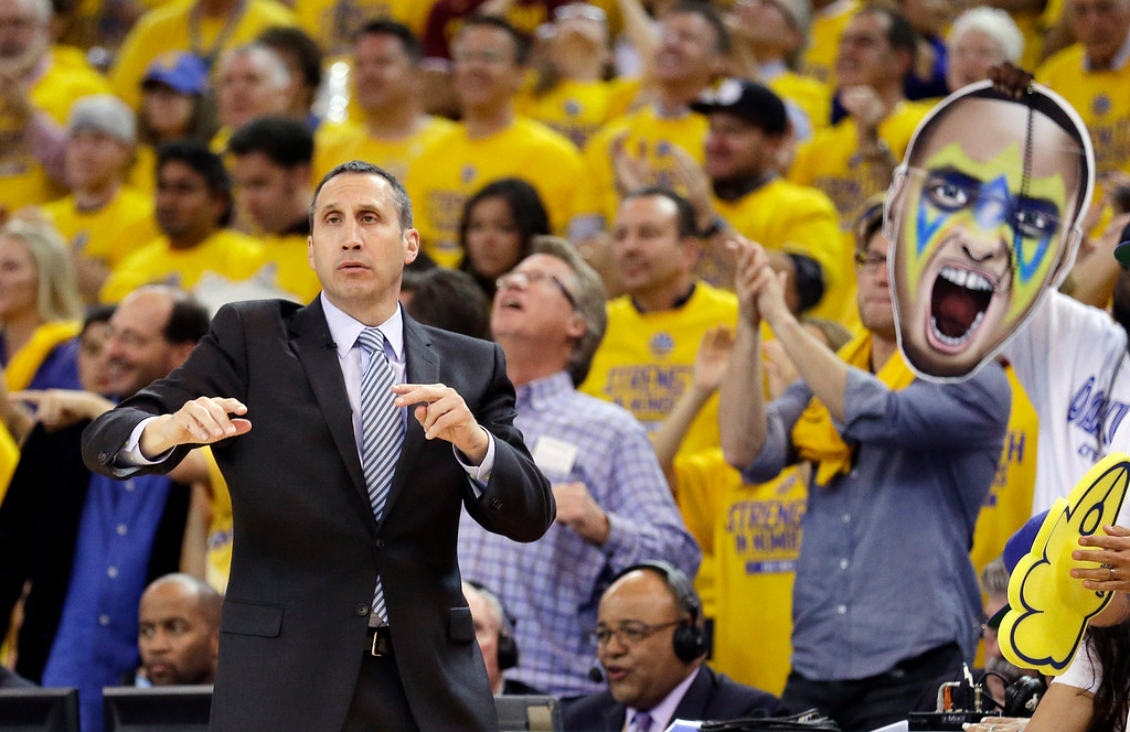 . Cleveland Cavaliers head coach David Blatt gestures as a fan holds up a large photo of Golden State Warriors guard Stephen Curry during the first half of Game 1 of basketball\'s NBA Finals between the Warriors and the Cavaliers in Oakland, Calif., Thursday, June 4, 2015. (AP Photo/Ben Margot)