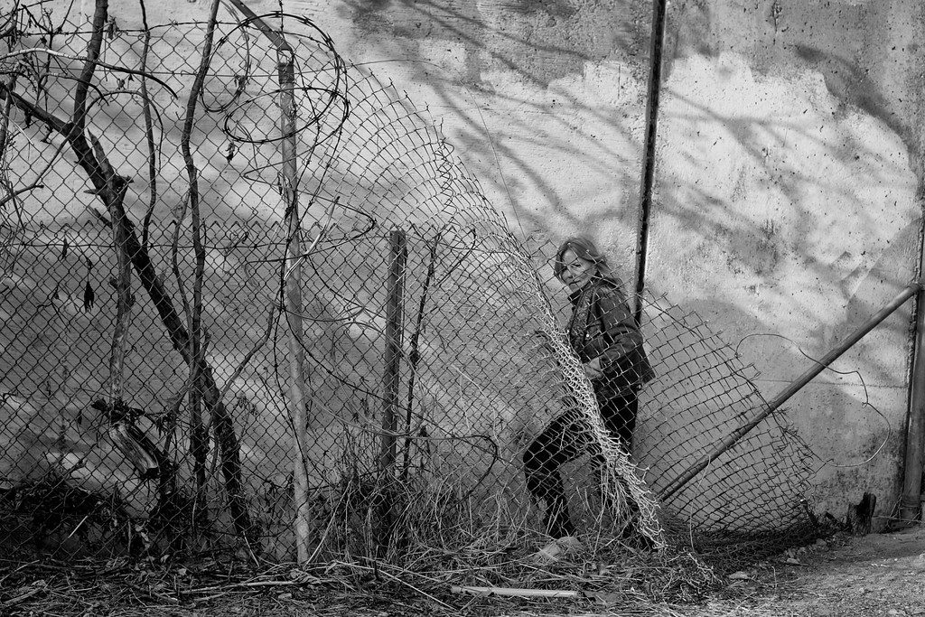 . Dorothy climbs over broken down fencing along the 210 Freeway as she heads into her camp.