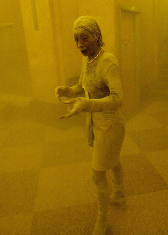 . This 11 September 2001 file photo shows Marcy Borders covered in dust as she takes refuge in an office building after one of the World Trade Center towers collapsed in New York. Borders was caught outside on the street as the cloud of smoke and dust enveloped the area.   AFP PHOTO/Stan HONDA