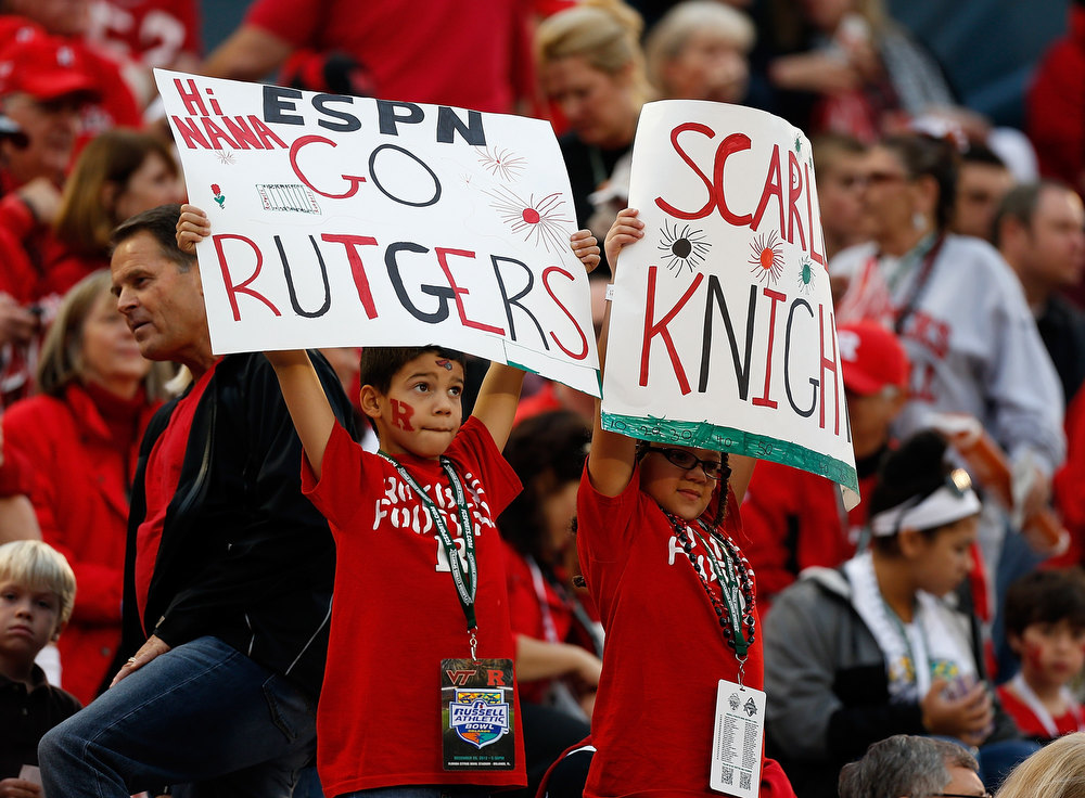 Description of . Fans of the Rutgers Scarlet Knights show their signs against the Virginia Tech Hokies during the Russell Athletic Bowl Game at the Florida Citrus Bowl on December 28, 2012 in Orlando, Florida.  (Photo by J. Meric/Getty Images)