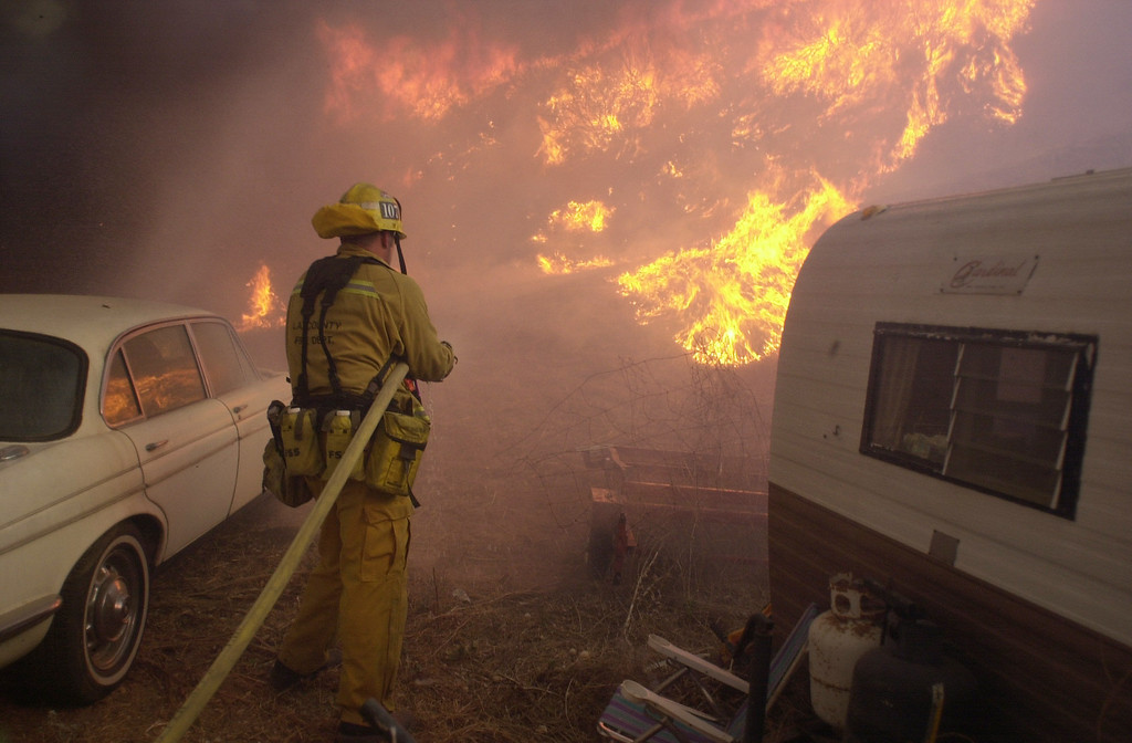 . VAL VERDE FIRE--A firefighter moves in to save a vehicle and motor home near a burning hillside near homes along San Martinez Grande road Friday afternoon.    10.24.03   Photo by David Crane/Daily News