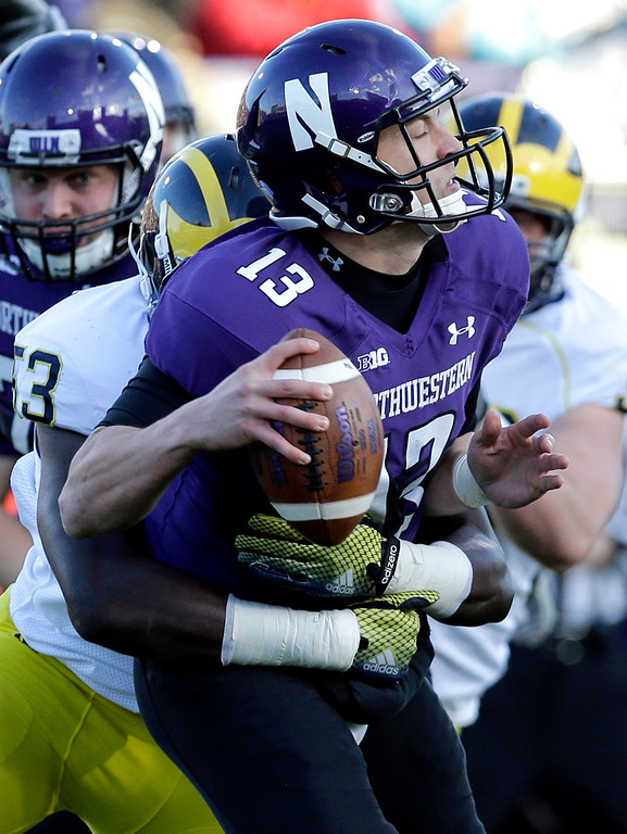 . Northwestern quarterback Trevor Siemian (13) is sacked by Michigan defensive end Mario Ojemdia (53) during the first half of an NCAA college football game in Evanston, Ill., Saturday, Nov. 8, 2014. (AP Photo/Nam Y. Huh)