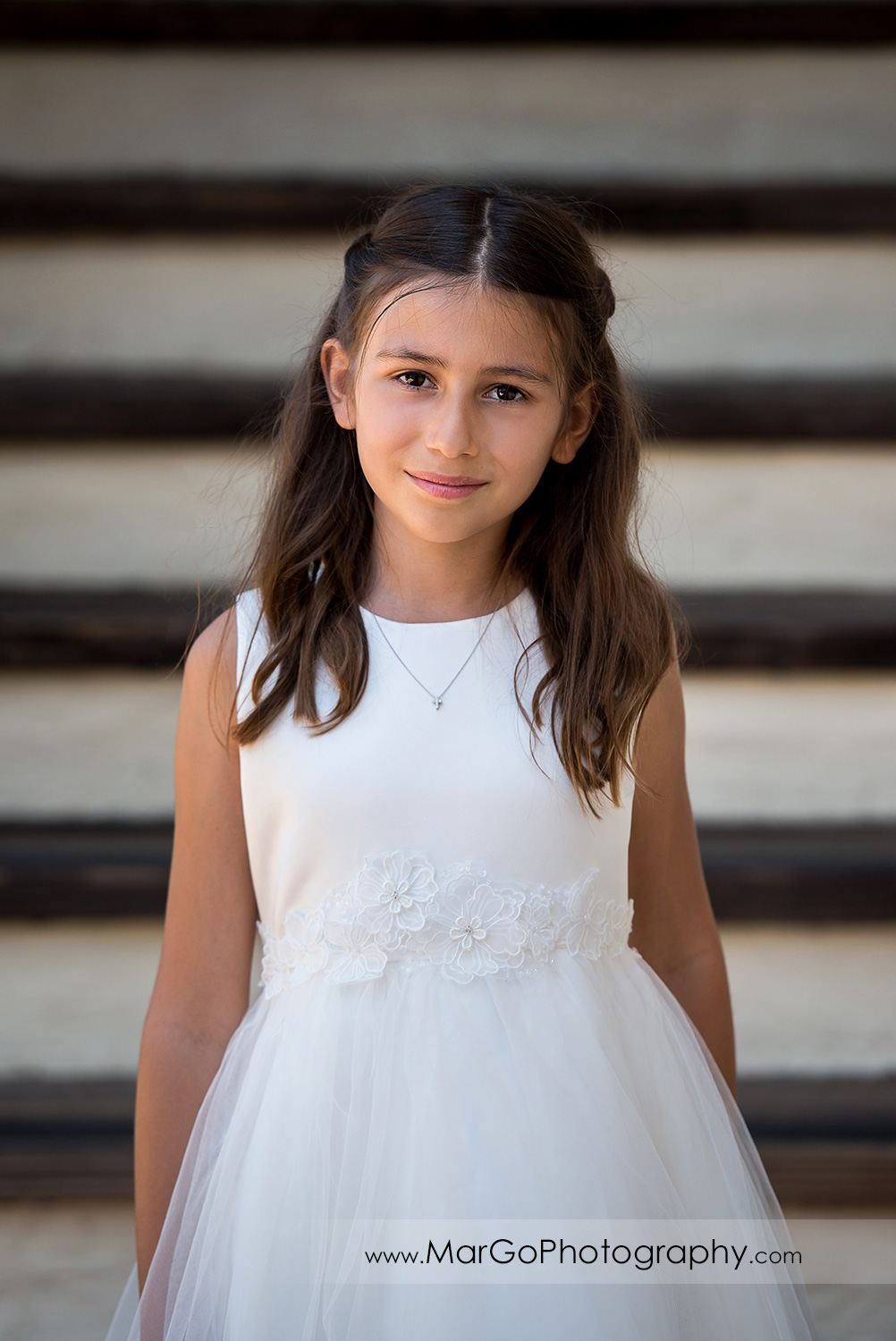 3/4 body portrait of first communion girl in white dress looking into camera at Cafe Wisteria in Menlo Park
