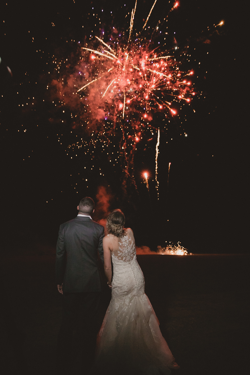 a newlywed couple looking at a fireworks display after their wedding
