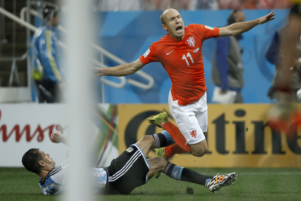 . Netherlands\' forward Arjen Robben (R) falls during the semi-final football match between Netherlands and Argentina of the FIFA World Cup at The Corinthians Arena in Sao Paulo on July 9, 2014. (ADRIAN DENNIS/AFP/Getty Images)