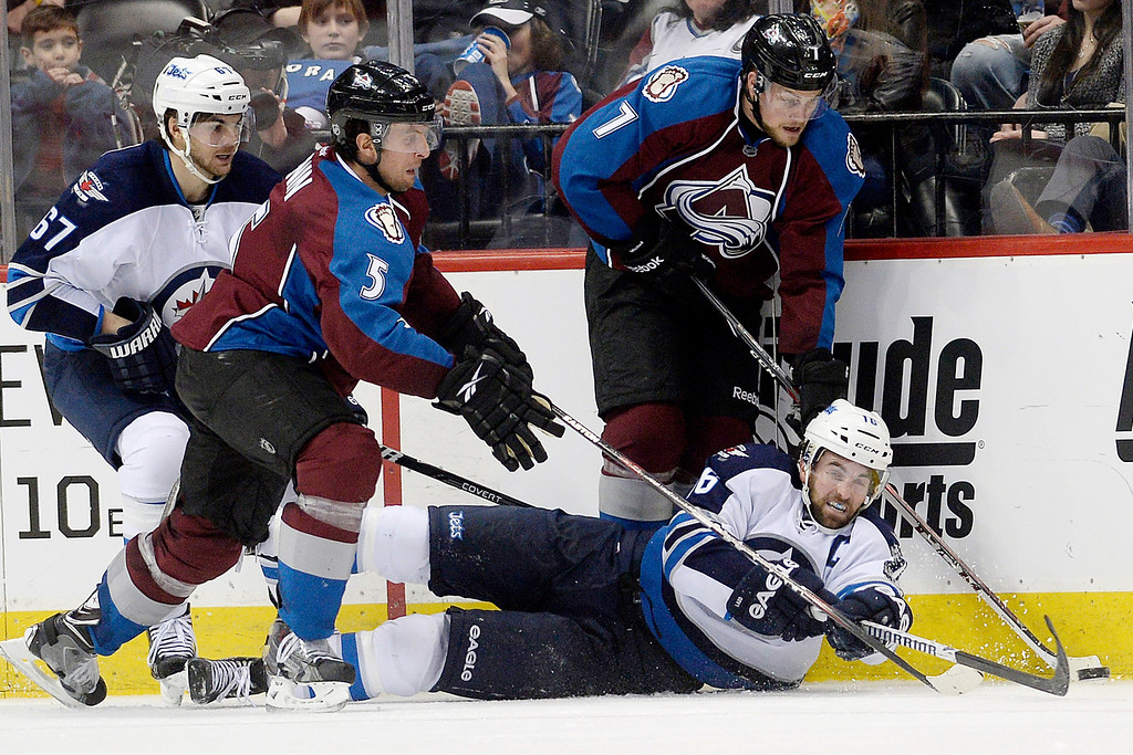 . Andrew Ladd (16) of the Winnipeg Jets hits the ice as he is defended by Nate Guenin (5) of the Colorado Avalanche and John Mitchell (7) of the Winnipeg Jets hits the ice against tehduring the Avs\' 3-2 win. (Photo by AAron Ontiveroz/The Denver Post)
