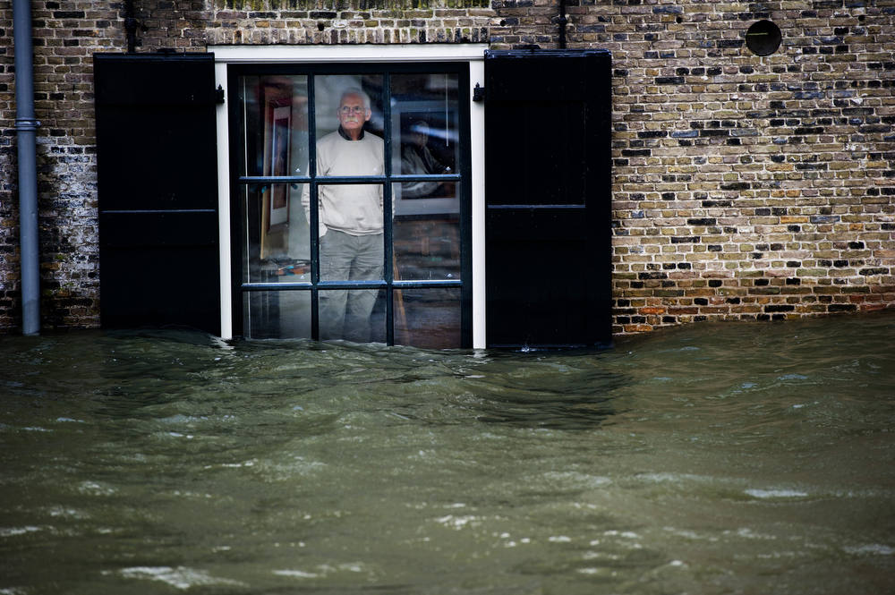 Description of . A Dutch local resident, standing in his house, looks to high waters level through his window, in Dordrecht on January 5, 2012. Gale force winds reaching up to 110 kilometres (about 70 miles) an hour as well as heavy rains are expected along the Dutch coast. About a quarter of the country sits below sea level.  ROBIN UTRECHT/AFP/Getty Images