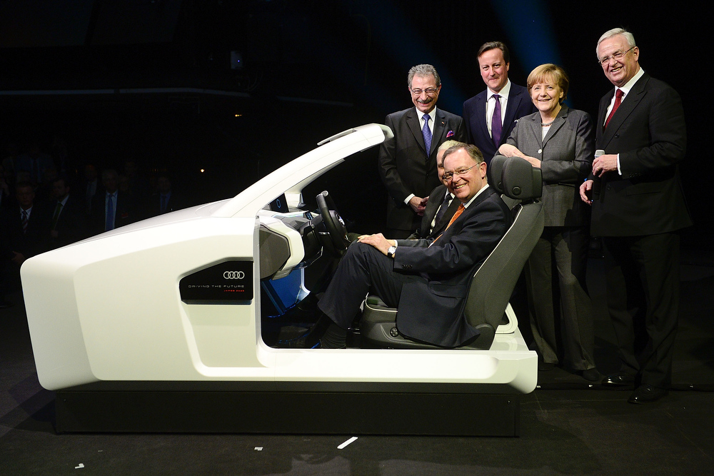 Description of . Bitkom President Dieter Kempf, Lower Saxony Governor Stephan Weil, British Prime Minister David Cameron, German Chancellor Angela Merkel and Volkswagen Group CEO Martin Winterkorn (L-R) stand next to a model of an Audi autonomic driven car during the opening evening of the 2014 CeBIT technology Trade fair on March 9, 2014 in Hanover, Germany. CeBIT is the world's largest technology fair and this year's partner nation is Great Britain.  (Photo by Nigel Treblin/Getty Images)
