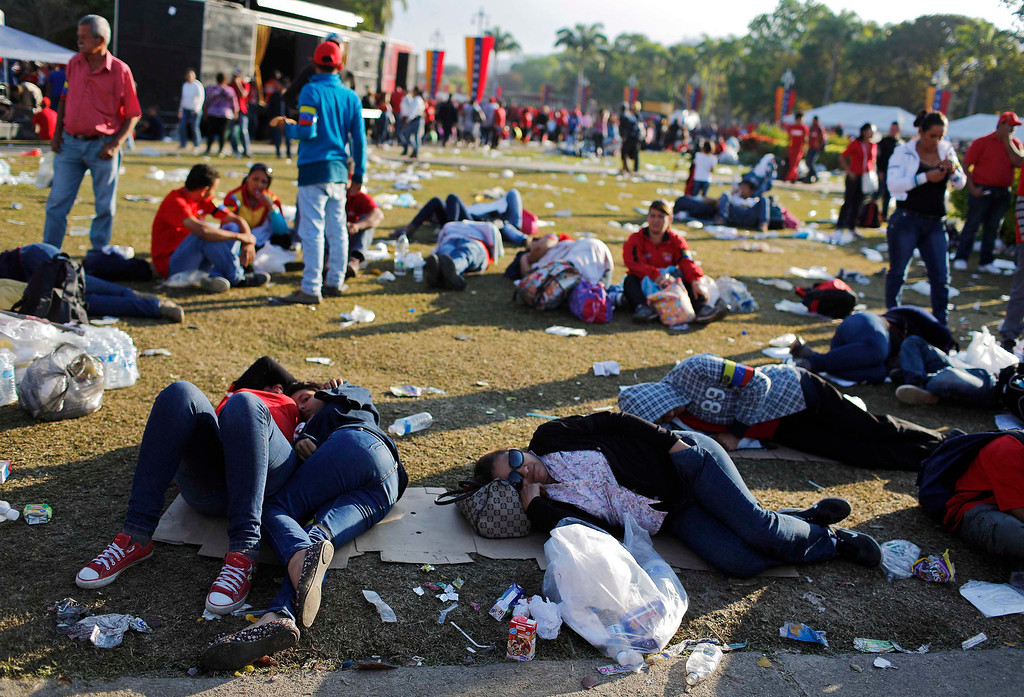 . Supporters of Venezuela\'s late President Hugo Chavez lie on the ground as they wait for a chance to view his body lying in state, at the military academy in Caracas March 8, 2013.    REUTERS/Tomas Bravo