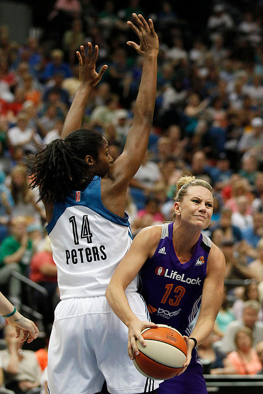 . Phoenix Mercury forward Penny Taylor (13) looks to make a pass against Minnesota Lynx forward Devereaux Peters (14) in the second half of a WNBA basketball game, (AP Photo/Stacy Bengs)