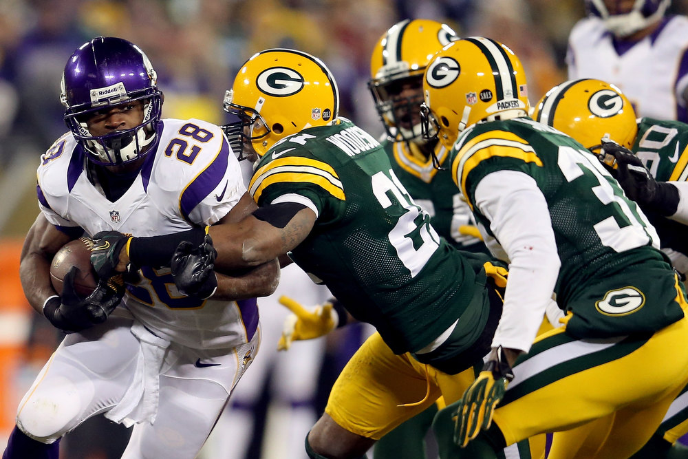 . Running back Adrian Peterson #28 of the Minnesota Vikings runs the ball as he is hit by strong safety Charles Woodson #21 of the Green Bay Packers in the first quarter during the NFC Wild Card Playoff game at Lambeau Field on January 5, 2013 in Green Bay, Wisconsin.  (Photo by Andy Lyons/Getty Images)