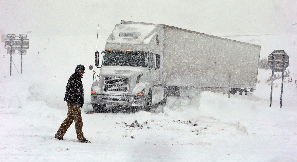 . Omer Odovsc walks in front of his tractor trailer that got stuck on the 219 off ramp leading to Rt. 391 in Boston, N.Y., Tuesday, Nov. 18, 2014. Parts of New York measured the season\'s first big snowfall in feet, rather than inches, on Tuesday as 3 feet of lake-effect snow blanketed the Buffalo area and forced the closure of a 132-mile stretch of the state Thruway. (AP Photo/The Buffalo News, Harry Scull Jr.)