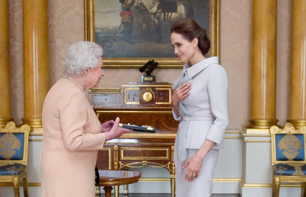 . U.S actress Angelina Jolie, right, is presented with the Insignia of an Honorary Dame Grand Cross of the Most Distinguished Order of St Michael and St George by Britain\'s Queen Elizabeth II at Buckingham Palace, London, Friday, Oct. 10, 2014.  (AP Photo/Anthony Devlin, PA Wire)