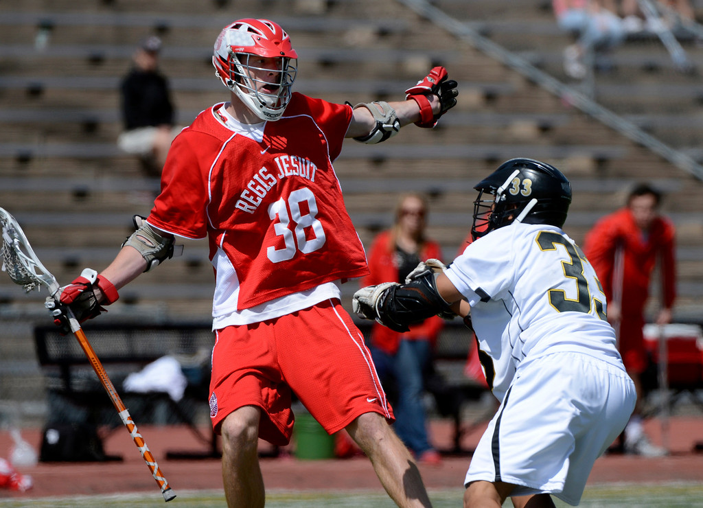 . LITTLETON, CO. - MAY 04:  Regis Jesuit\'s Chase Konkel keeps the ball from Arapahoe\'s Peter Neenan during the varsity high school lacrosse game between the Arapahoe Warriors and the Regis Jesuit Raiders in Littleton, CO May 04, 2013. The Raiders won the game 9-6.  (Photo By Craig F. Walker/The Denver Post)